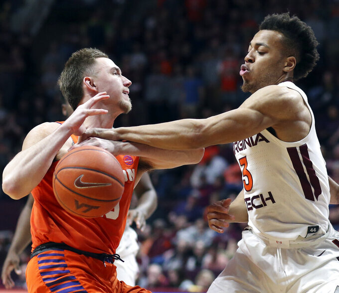 Clemson's Curran Scott, left, has the ball stripped from him by Virginia Tech's Wabissa Bede (3 ) during the first half of an NCAA college basketball game Wednesday, March 4, 2020, in Blacksburg, Va. (Matt Gentry/The Roanoke Times via AP)