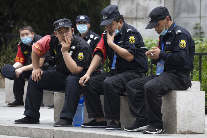 Security guards remove their masks for a smoke break in Beijing on Wednesday, May 6, 2020. China on Wednesday reported just two new cases of the coronavirus and no deaths as it continues to reopen more sectors of the society. (AP Photo/Ng Han Guan)
