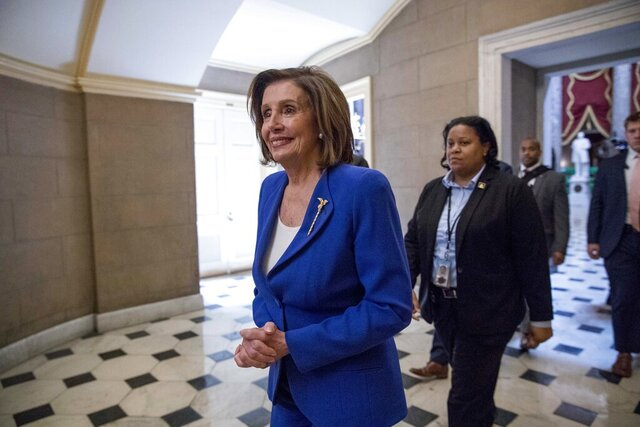 In this March 27, 2020, photo, House Speaker Nancy Pelosi of Calif., walks to her office after signing the Coronavirus Aid, Relief, and Economic Security (CARES) Act on Capitol Hill in Washington. President Donald Trump wants to spend $2 trillion on infrastructure projects to create jobs and help the collapsing economy rebuild from the coronavirus' stunning blows. Pelosi says that seems about right. Sounds like the prelude to a bipartisan deal. Except that when it comes to trying to upgrade the country's road, rail, water and broadband systems, Washington frequently veers off the tracks — usually over the bill's contents and how to pay for it. (AP Photo/Andrew Harnik)