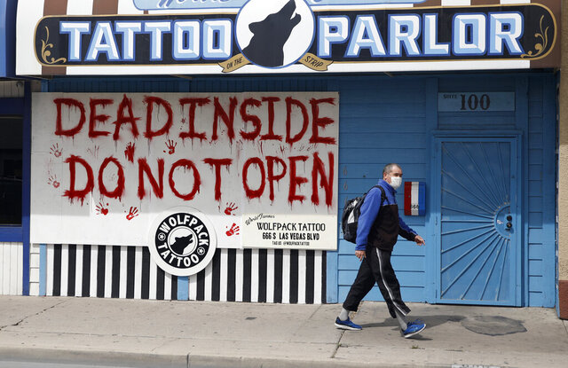 FILE - In this March 25, 2020, file photo, a man walks by a tattoo parlor closed and boarded up due to coronavirus in Las Vegas. State inspectors say they found one in four bars, businesses, gyms and salons in and around Las Vegas not complying with Nevada Gov. Steve Sisolak's order for people to use face coverings in public places to stem the spread of the coronavirus. The state Occupational Safety and Health Administration said Thursday, July 2, that compliance statewide was about 80% since the governor's mask mandate took effect June 26. (AP Photo/John Locher, File)