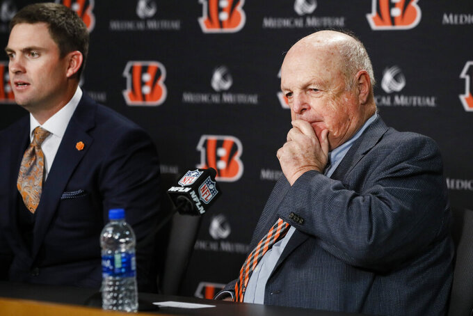 Cincinnati Bengals owner Mike Brown, right, listens as the new head coach Zac Taylor, left, answers reporter's questions during a news conference, Tuesday, Feb. 5, 2019, in Cincinnati. After 16 years without a playoff win under Marvin Lewis, the Bengals decided to try something different. But they had to wait more than a month before hiring Zac Taylor as their next coach in hopes of ending a long streak of futility. (AP Photo/John Minchillo)