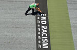 A worker prepares a sticker reading 'End Racism' on the track before the Austrian Formula One Grand Prix race at the Red Bull Ring racetrack in Spielberg, Austria, Sunday, July 5, 2020. (Joe Klamar/Pool via AP)