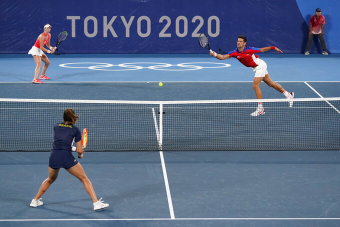 Novak Djokovic, right, and Nina Sojanovic, of Serbia, return to Luisa Stefani, bottom left, and Marcelo Melo, of Brazil, during a first round mixed doubles tennis match at the 2020 Summer Olympics, Wednesday, July 28, 2021, in Tokyo, Japan. (AP Photo/Patrick Semansky)