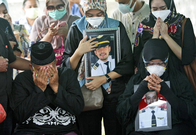 Relatives weep as they pray during the burial of Fadly Satrianto, a victim of the crash of Sriwijaya Air flight SJ-182 in Surabaya, East Java, Indonesia, Friday, Jan. 15, 2021. More searchers and rescuers joined the search Friday for wreckage and victims from the Indonesian plane that crashed last weekend in the Java Sea. (AP Photo/Trisnadi)