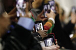 FILE - In this Feb. 27, 2019 file photo, guests use with their cell phones to record the Mugler ready to wear Fall-Winter 2019-2020 collection, that was presented in Paris. The coronavirus pandemic has instilled extra unpredictability into the already fickle Paris Fashion Week. After first canceling the July shows for menswear and Haute Couture, the French fashion federation has now organized an unprecedented schedule of digital-only events instead. (AP Photo/Kamil Zihnioglu, File)