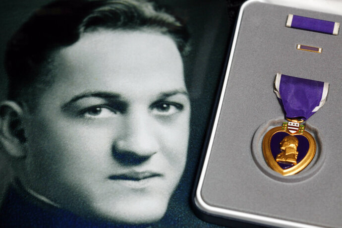 FILE - This May 6, 2010 file photo, shows a portrait of Coast Guard Lt. Thomas J.E. Crotty next to a Purple Heart medal, one of several medals presented posthumously in Buffalo, N.Y. The remains of Crotty, a Coast Guardsman who died as a prisoner of war during World War II, has returned home to Buffalo for a funeral his relatives have been awaiting for decades. His remains were identified in September, 77 years after his death from diphtheria in a Japanese POW camp. (AP Photo/David Duprey, File)