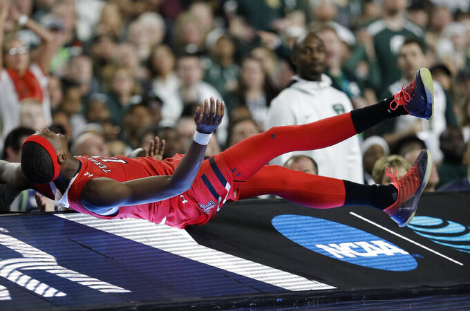Texas Tech forward Tariq Owens lands on the scorers table while trying to save a ball from going out of bounds during the first half against Michigan State in the semifinals of the Final Four NCAA college basketball tournament, Saturday, April 6, 2019, in Minneapolis. (AP Photo/David J. Phillip)
