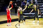 Ohio State guard Duane Washington Jr. (4) makes a three-point basket as Iowa's Connor McCaffery (30) defends in the second half during an NCAA college basketball game Thursday, Feb. 4, 2021, in Iowa City, Iowa. (Joseph Cress/Iowa City Press-Citizen via AP)