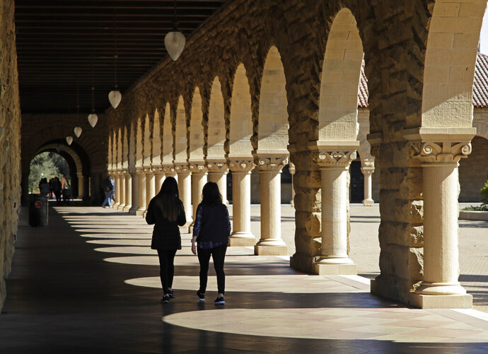 FILE - In this March 14, 2019, file photo students walk on the Stanford University campus in Stanford, Calif.  Colleges are giving out more aid based on students' accomplishments, not their financial need. And they're targeting high-income students as the recipients of this money. Colleges are competing for these high-income students in part to boost their rankings and reputations. (AP Photo/Ben Margot, File)