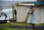 Irma Torres, a resident of the El Negro coastal sector, walks outside her home before the arrival of Tropical Storm Karen, in Yabucoa, Puerto Rico, Tuesday, Sept. 24, 2019. Karen regained tropical storm strength as it swirled toward Puerto Rico, where it's expected to bring heavy rains and strong winds. (AP Photo/Carlos Giusti)