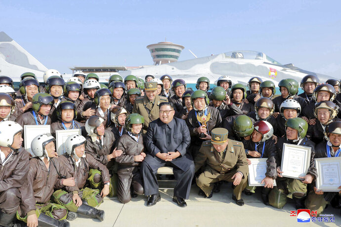 In this undated photo provided on Saturday, Nov. 16, 2019 by the North Korean government, North Korean  leader Kim Jong Un, front center, poses with pilots during his inspection of a flight demonstration of military aircraft at an airfield in North Korea. Independent journalists were not given access to cover the event depicted in this image distributed by the North Korean government. The content of this image is as provided and cannot be independently verified. Korean language watermark on image as provided by source reads: