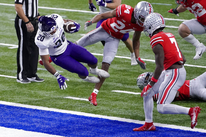 Northwestern running back Cam Porter (20) scores past Ohio State cornerback Shaun Wade (24) and cornerback Sevyn Banks (7) during the first half of the Big Ten championship NCAA college football game, Saturday, Dec. 19, 2020, in Indianapolis. (AP Photo/AJ Mast)