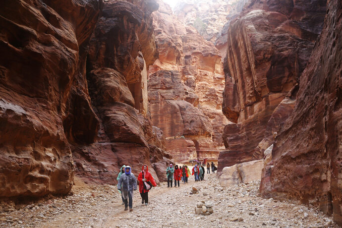 FILE - In this Feb. 13, 2017 file photo, tourists brave a rare rainstorm in plastic ponchos to hike deeper into Jordan's famous Petra archaeological park, southern Jordan. In ancient times, Arab tribesmen dug diversion tunnels to protect their low-lying trading post of Petra against desert flash floods. More than two millennia later, an alarm system warns visitors if flood water rushes toward what has become Jordan's main tourist attraction. (AP Photo/Sam McNeil, File)