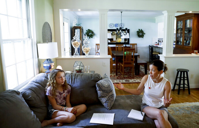 In this Thursday, May 3, 2018 photo, Sandy Nissenbaum, right, and her daughter, Nora Nissenbaum, 12, talk during an interview with The Associated Press in Wayne, Pa. The case of a suburban Philadelphia boy who was quietly allowed to return to class after being accused of making a shooting threat has thrown a spotlight on the hard decisions school authorities must make. Nora Nissenbaum who says the boy bullied her has withdrawn from class for fear of him.  (AP Photo/Matt Slocum)