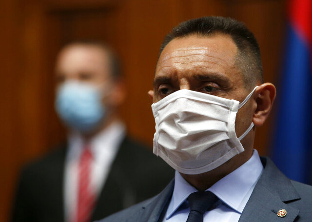 In this Tuesday, April 28, 2020. file photo, Serbia Defense Minister Aleksandar Vulin wearing a mask to protect against coronavirus attends the session in Belgrade, Serbia. The Defense Ministry says Serbia's Defense Minister Aleksandar Vulin has tested positive with the coronavirus. (AP Photo/Darko Vojinovic, File)