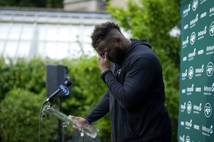 New York Jets' defensive lineman John Franklin-Myers is overcome with emotion as he speaks about signing his new contract during a press conference after an NFL practice session at Hanbury Manor Marriott Hotel and Country Club near the town of Ware in south east England, Friday, Oct. 8, 2021. The New York Jets are preparing for an NFL regular season game against the Atlanta Falcons in London on Sunday. (AP Photo/Matt Dunham)