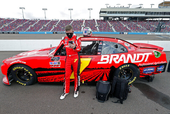 Justin Allgaier looks at his phone as he stands with his race car on pit road prior to the NASCAR Xfinity Series auto race at Phoenix Raceway, Saturday, Nov. 7, 2020, in Avondale, Ariz. (AP Photo/Ralph Freso)