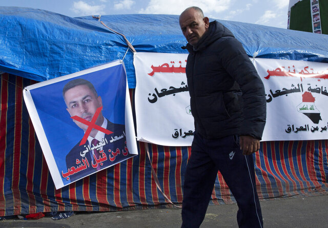 A protester walks past a poster with a defaced picture of the governor of the southern Basra province Asaad al-Eidani and Arabic that reads