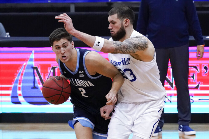 Villanova guard Collin Gillespie (2) drives against Seton Hall forward Sandro Mamukelashvili (23) during the second half of an NCAA college basketball game, Saturday, Jan. 30, 2021, in Newark, N.J. (AP Photo/Mary Altaffer)