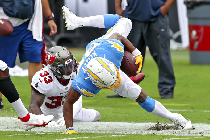 Tampa Bay Buccaneers free safety Jordan Whitehead (33) trips up Los Angeles Chargers running back Joshua Kelley (27) after a run during the first half of an NFL football game Sunday, Oct. 4, 2020, in Tampa, Fla. (AP Photo/Mark LoMoglio)