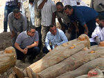 """This photo provided by the Egyptian Ministry of Antiquities shows Egyptian  Minister of Antiquities Khaled el-Anany, foreground left, looking at recently discovered ancient colored coffins with inscriptions and paintings, in the southern city of Luxor, Egypt, Tuesday, Oct. 15, 2019. The ministry said archeologists found at least 20 wooden coffins in the Asasif Necropolis, describing it as one of the """"biggest and most important"""" discoveries in recent years.  (Egyptian Ministry of Antiquities via AP)"""