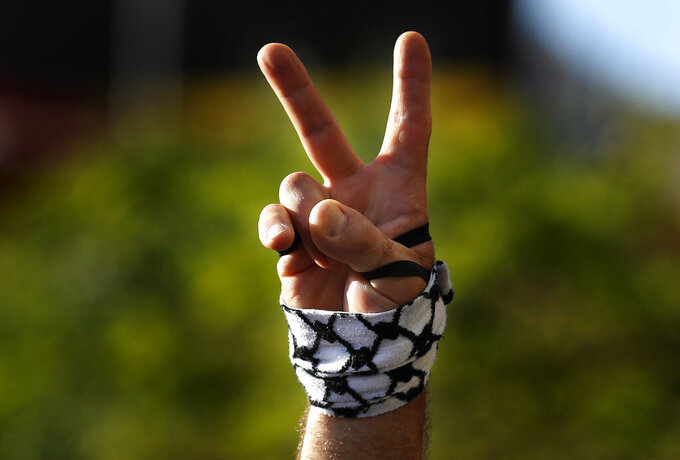 A protester flashes a victory sign with a representation of a Palestinian headscarf on his hand, during a protest in support of Palestinians in the latest round of violence between Palestinians and Israelis, in Beirut, Lebanon, Tuesday, May 11, 2021. A confrontation between Israel and Hamas sparked by weeks of tensions in contested Jerusalem escalated Tuesday. (AP Photo/Hussein Malla)