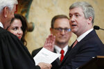 State Treasurer David McRae recites the oath of office as he is sworn into office by Mississippi Supreme Court Chief Justice Michael Randolph, while wife Katherine McRae, second from left, holds their family Bible, in House chambers at the Mississippi Capitol in Jackson, Miss., Thursday, Jan. 9, 2020. (AP Photo/Rogelio V. Solis)