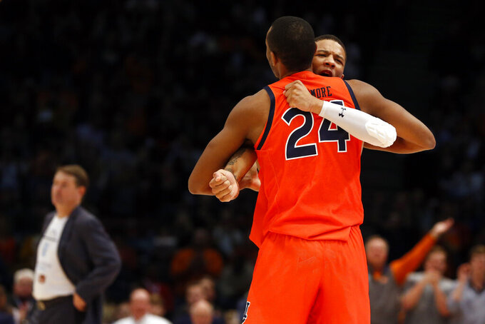 Auburn forward Anfernee McLemore (24) hugs guard Samir Doughty (10) after making a three-point basket as Saint Louis head coach Travis Ford, background left, reacts during the second half of an NCAA college basketball game Saturday, Dec. 14, 2019, in Birmingham, Ala. (AP Photo/Butch Dill)