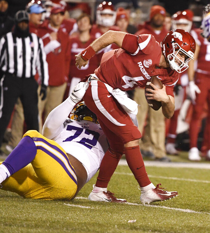 Arkansas quarterback Ty Storey tries to shake LSU defender Tyler Shelvin during the second half of an NCAA college football game, Saturday, Nov. 10, 2018, in Fayetteville, Ark. LSU won, 24-17. (AP Photo/Michael Woods)