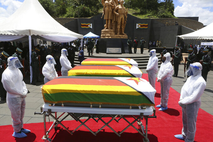 Pallbearers stand next to coffins of three top government officials at their burial at the National Heroes acre in Harare, Wednesday, Jan, 27, 2021. Zimbabwe on Wednesday buried three top officials who succumbed to COVID-19, in a single ceremony at a shrine reserved almost exclusively for the ruling elite as a virulent second wave of the coronavirus takes a devastating toll on the country.( AP Photo/Tsvangirayi Mukwazhi)