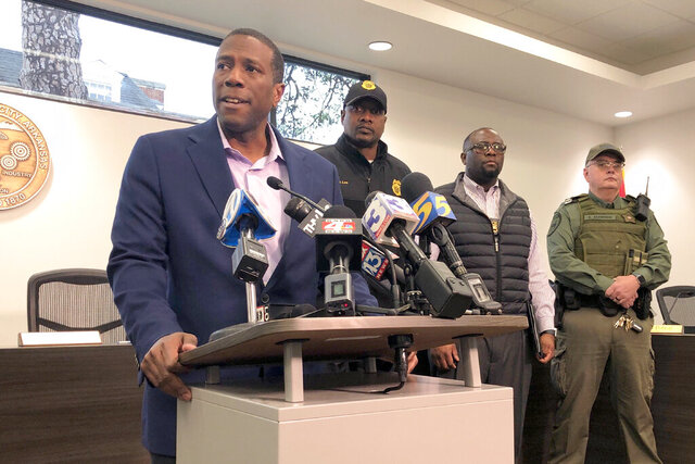 Forrest City, Ark., Mayor Cedric Williams, left, holds a news conference after two police officers were wounded and a gunman was killed in an exchange of gunfire at a Walmart store in eastern Arkansas Monday morning Feb. 10, 2020. Williams said that the officers were hospitalized soon after the shooting at the store about 45 miles west of Memphis. (AP Photo/Adrian Sainz)