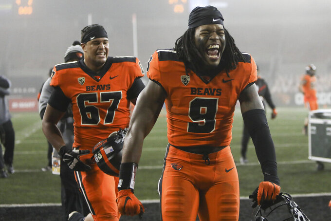 Oregon State's Hamilcar Rashed Jr. (9) and Joshua Gray (67) celebrate the team's 41-38 win over Oregon following an NCAA college football game in Corvallis, Ore., Friday, Nov. 27, 2020. (AP Photo/Amanda Loman)