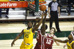 Baylor guard Davion Mitchell (45) drives to the basket as Oklahoma forward Kur Kuath, center, defends and Oklahoma guard Austin Reaves (12) looks on during the first half of an NCAA college basketball game on Wednesday, Jan. 6, 2021, in Waco, Texas. (AP Photo/Ray Carlin)