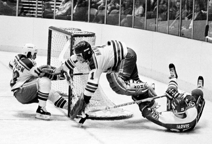 FILE - In this Dec. 7, 1983, file photo, Washington Capitals' Doug Jarvis (25), right, scores a goal against New York Rangers goalie Glen Hanlon during the first period of an NHL hockey game at Madison Square Garden in New York. The puck slides into the goal off the skates of Rangers' Mark Pavelich, left. Pavelich has died at a treatment center for mental illness. Officials in Anoka County, Minnesota, confirmed Friday, March 5, 2021, that Pavelich, 63, died at Eagle's Healing Nest in Sauk Centre, Minn., Thursday morning. The cause and manner of death are still pending. (AP Photo/Ron Frehm, File)