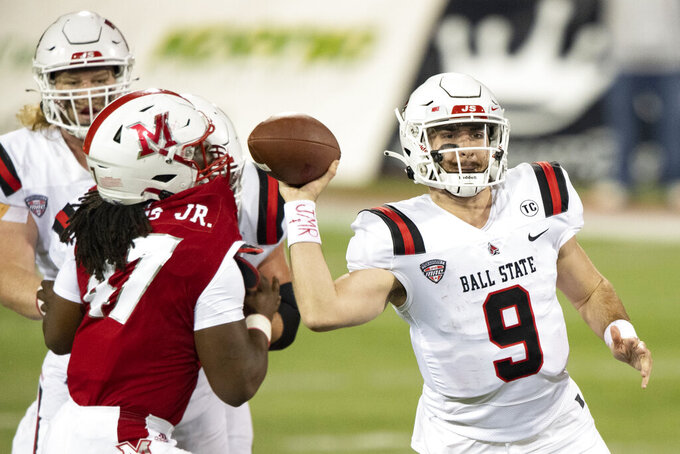 FILE - In this Wednesday, Nov. 4, 2020 file photo, Ball State Cardinals quarterback Drew Plitt (9) makes a pass during an NCAA football game against the Miami (Oh) Redhawks in Oxford, Ohio. Quarterback Drew Plitt returns for a sixth season. Will Jones and Tye Evans, who split carries during the second half of last season, also are back. Justin Hall and Yo'Heinz Tyler are expected to again form one of the league's top receiving tandems and all five offensive line starters remain in place.(AP Photo/Emilee Chinn, File)