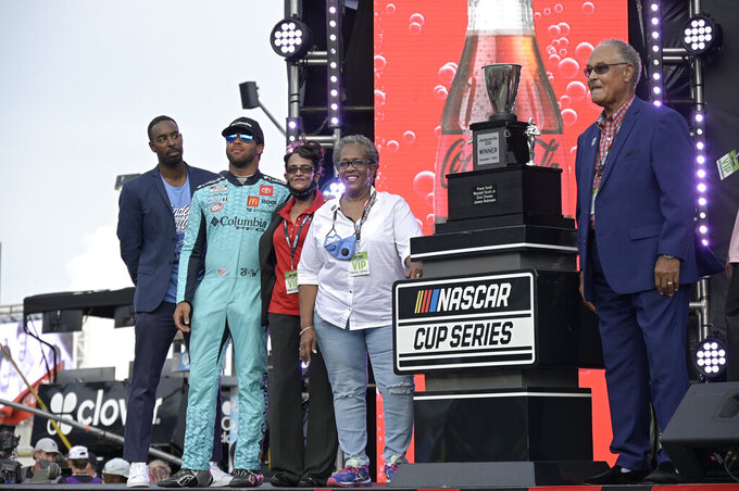 Wendell Scott's family is presented a trophy before a NASCAR Cup Series auto race at Daytona International Speedway, Saturday, Aug. 28, 2021, in Daytona Beach, Fla. Scott's son Frank Scott, right, stands with family members and guest driver Bubba Wallace, second from left. NASCAR presented Scott's family a custom trophy commemorating his historic 1963 victory. Scott was the only Black driver to win a race at NASCAR's top level. (AP Photo/Phelan M. Ebenhack)