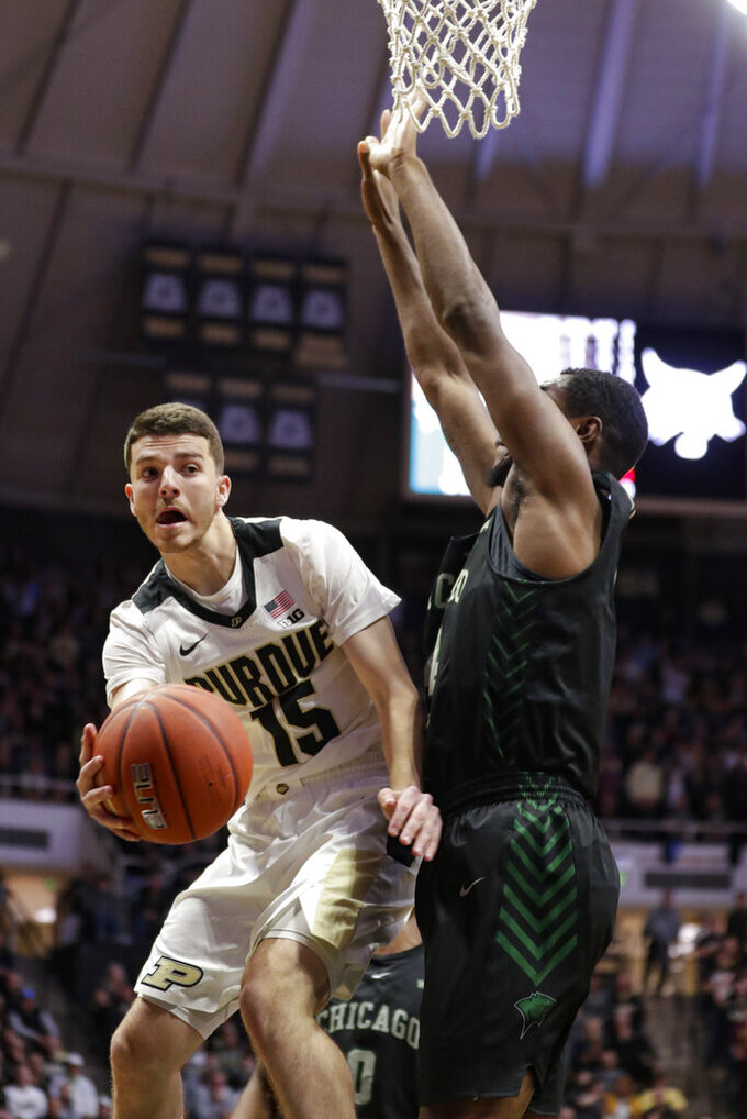 Purdue guard Tommy Luce (15) makes a pass around Chicago State forward Ke'Sean Davis (4) during the second half of an NCAA college basketball game in West Lafayette, Ind., Saturday, Nov. 16, 2019. Purdue defeated Chicago State 93-49. (AP Photo/Michael Conroy)