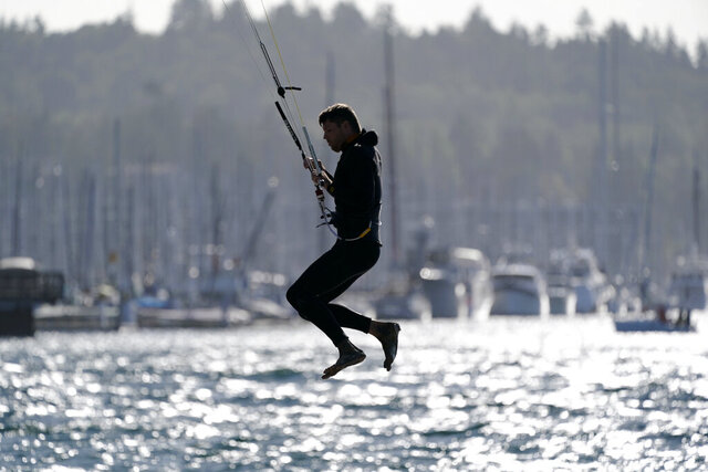 Martin Anderson is briefly suspended in the air as he tests the wind before heading out into Puget Sound on a kiteboard Tuesday, Oct. 13, 2020, in Seattle. The National Weather Service issued a wind advisory for much of Tuesday around Puget Sound and on the Washington coast. Southwest winds in the afternoon could reach 30 mph, with gusts of up to 50 mph, according to the National Weather Service. (AP Photo/Elaine Thompson)