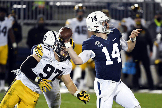 Penn State quarterback Sean Clifford (14) throws a touchdown pass to wide receiver Jahan Dotson as Iowa defensive lineman Zach VanValkenburg (97) pressures him during the third quarter of an NCAA college football game in State College, Pa., on Saturday, Nov. 21, 2020. Iowa defeated Penn State 41-21. (AP Photo/Barry Reeger)
