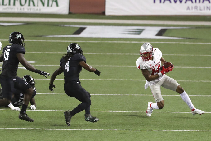New Mexico cornerback Michael LoVett III (14) tries to run around the Hawaii defense during the first quarter of an NCAA college football game, Saturday, Nov. 7, 2020, in Honolulu. (AP Photo/Marco Garcia)