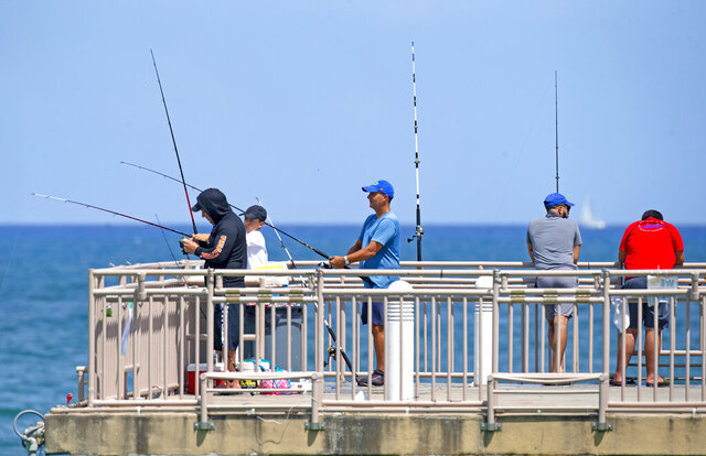 People fishing at the Newport Fishing Pier in Sunny Isles Beach as the coronavirus pandemic continues on Sunday, Sept. 6, 2020. (David Santiago/Miami Herald via AP)