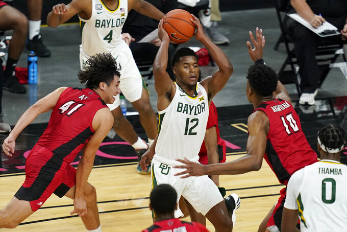 Baylor's Jared Butler (12) passes around Louisiana-Lafayette's Brayan Au (41) and Theo Akwuba (10) during the first half of an NCAA college basketball game Saturday, Nov. 28, 2020, in Las Vegas. (AP Photo/John Locher)