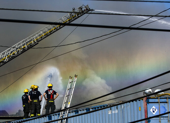 Authorities work to extinguish a junkyard fire in the Kensington neighborhood of Philadelphia, Wednesday, July 11, 2018. The fire was reported around 8:30 p.m. Tuesday and spewed thick smoke and flames that could be seen for miles. Authorities say the burning materials consisted mainly of metal, wood and paper. (AP Photo/Matt Rourke)