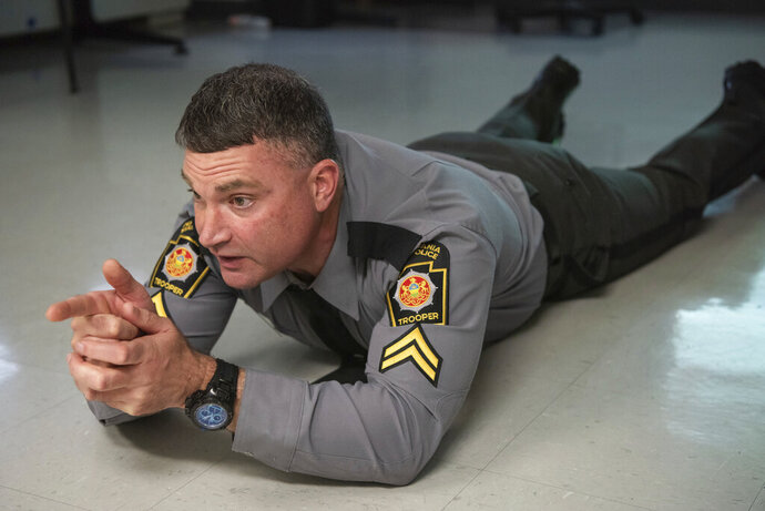 Pennsylvania State Police Cpl. Kevin Selverian, a use of force specialist, poses as an armed suspect during a use of force presentation at the Troop M Barracks in Bethlehem, Pa., on Thursday, Nov. 12, 2020. (Michele Haddon/Bucks County Courier Times via AP)