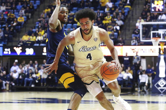 CORRECTS AKRON PLAYER TO TYLER CHEESE, INSTEAD OF CHANNEL BANKS - Akron's Tyler Cheese is defended by West Virginia's Taz Sherman during an NCAA college basketball game, Friday, Nov. 8, 2019, in Morgantown, W.Va. (AP Photo/Kathleen Batten)