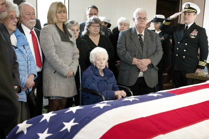 Rita Mendonsa, center, sits in front of her husband George's flag-draped casket during funeral services at St. Columba Cemetery in Middletown, R.I., Friday, Feb. 22, 2019. George Mendonsa, the sailor sailor photographed kissing a woman in Times Square at the end of World War, died Sunday at age 95. (AP Photo/Michael Dwyer)