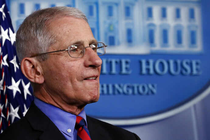 Dr. Anthony Fauci, director of the National Institute of Allergy and Infectious Diseases, listens as President Donald Trump speaks about the coronavirus in the James Brady Briefing Room, Wednesday, March 25, 2020, in Washington. (AP Photo/Alex Brandon)