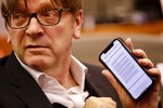 European Parliament Brexit chief Guy Verhofstadt shows on his phone a letter sent to the EU from British Prime Minister Boris Johnson during a meeting of the Committee on Petitions at the European Parliament, Wednesday, Oct. 2, 2019. British Prime Minister Boris Johnson sent to Brussels what he says is the U.K.'s final offer for a Brexit deal, with the date set for Britain's departure less than a month away. (AP Photo/Olivier Matthys)