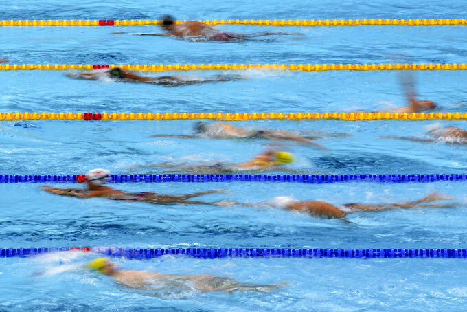 FILE - In this July 21, 2021, file photo, athletes exercise during a swimming training session at the Tokyo Aquatics Centre at the 2020 Summer Olympics in Tokyo, Japan. With hundreds of swimmers scrambling to get their warmup done at the same time, multiple athletes in each lane, everyone diving over one another and some competitors using snorkels, kickboards and other paraphernalia, warmup is organized chaos. (AP Photo/Matthias Schrader, File)