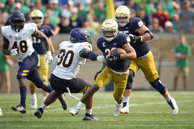 Notre Dame running back Kyren Williams (23) runs in front of Toledo linebacker Jonathan Jones (30) in the second half of an NCAA college football game in South Bend, Ind., Saturday, Sept. 11, 2021. Notre Dame won 32-29. (AP Photo/AJ Mast)